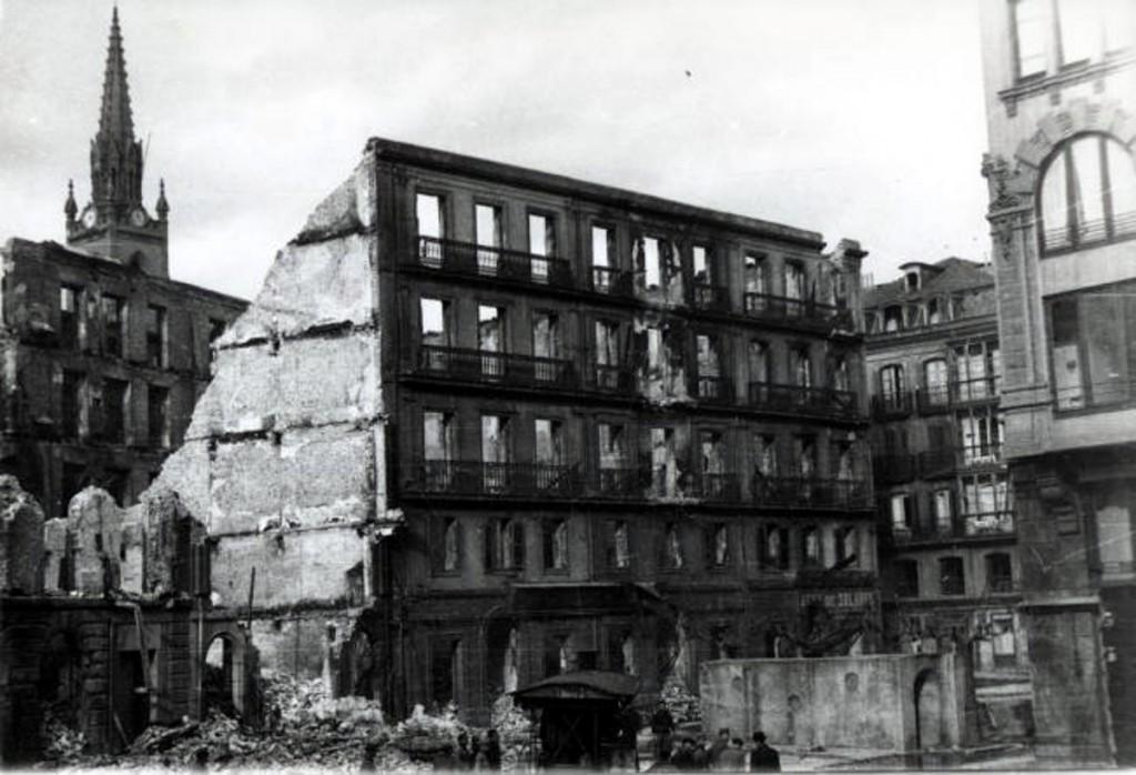 Plaza del príncipe, con la Iglesia de los Jesuitas al fondo. Nótese que la pequeña construcción en la parte inferior derecha es la entrada al refugio antiaéreo, hoy visitable. 1941, DM.