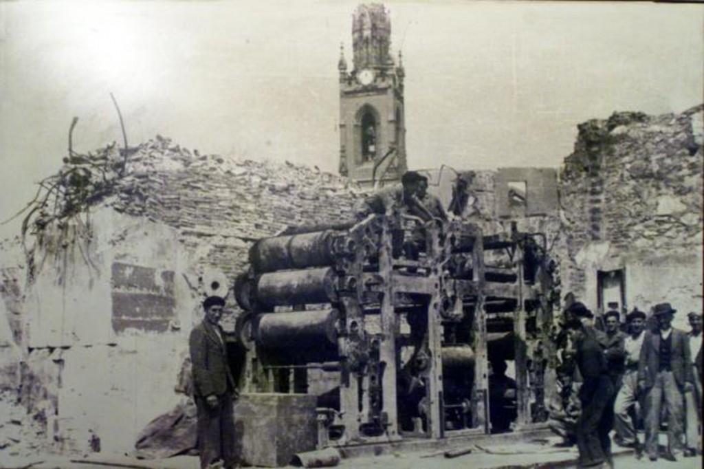 La sede de El Diario Montañés situada en la calle Arcillero, desapareció en el incendio. Los restos de la rotativa son observados, con la torre de Los Jesuitas, al fondo. 1941, DM.